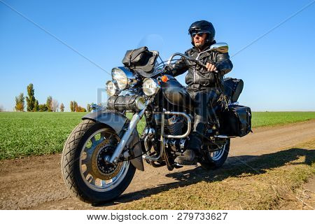 Motorcycle Driver Riding Custom Chopper Bike on an Autumn Dirt Road in the Green Field. Adventure Concept.