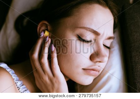 Woman Sleeping On The Bed With Earplugs In The Ears