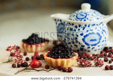 Sweet cupcakes with fresh organic strawberries on wooden table