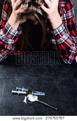 Young Woman And Syringe With Heroin Or Cocaine On Table