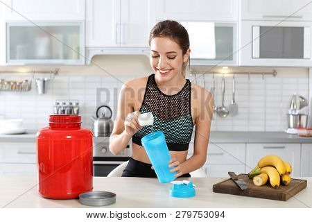 Young Woman Preparing Protein Shake At Table In Kitchen