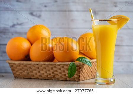 Glass Of Freshly Squeezed Orange Juice Standing On Light Background With A Fresh Oranges.