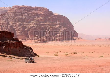 Safari in Wadi Rum desert, Jordan, Middle East. Tourists in the car ride on off-road on sand among the beautiful rocks