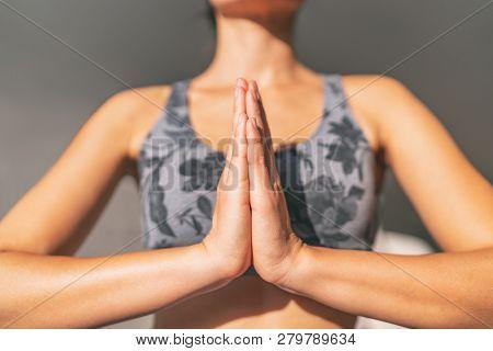 Yoga namaste woman meditating yoga mudra with closed hands together in prayer pose praying for gratitude. Zen meditation wellness in morning sun.