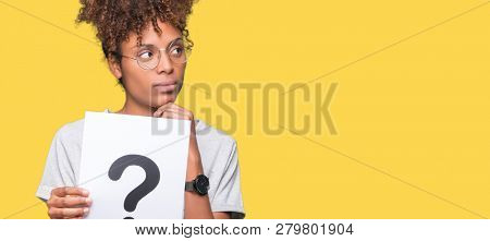 Young african american woman holding paper with question mark over isolated background serious face thinking about question, very confused idea