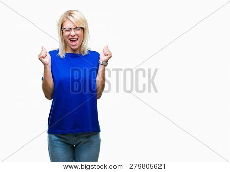Young beautiful blonde woman wearing glasses over isolated background excited for success with arms raised celebrating victory smiling. Winner concept.