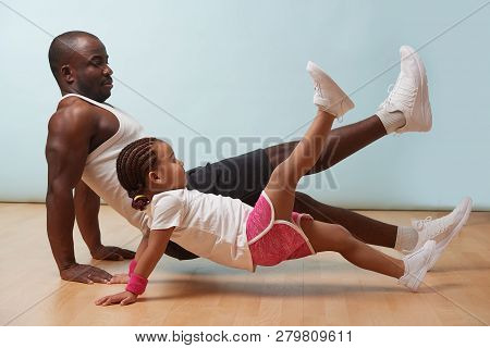 Handsome Black Young Father And His Cute Little Daughter Are Doing Reverce Plank With Leg Raise On T