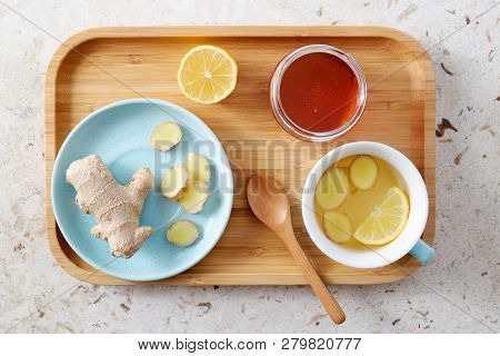 Lemon and ginger tea with honey. Wooden tray of honey lemon tea with fresh ginger root.