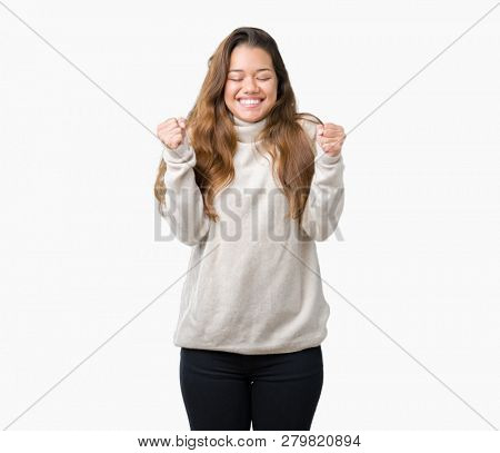 Young beautiful brunette woman wearing turtleneck sweater over isolated background excited for success with arms raised celebrating victory smiling. Winner concept.