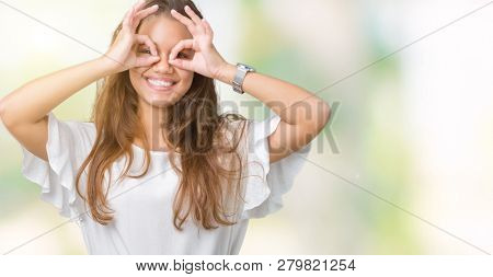 Young beautiful brunette business woman over isolated background doing ok gesture like binoculars sticking tongue out, eyes looking through fingers. Crazy expression.