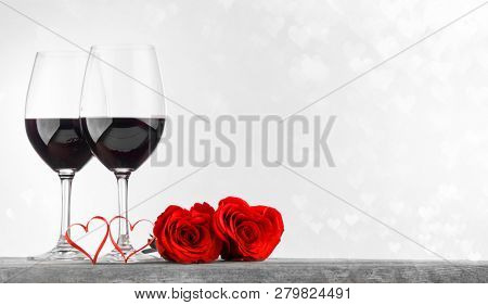 Two glasses of red wine , roses and ribbon hearts for Valentine day