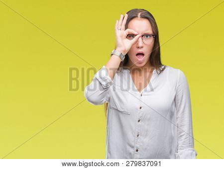 Young caucasian beautiful business woman wearing glasses over isolated background doing ok gesture shocked with surprised face, eye looking through fingers. Unbelieving expression.