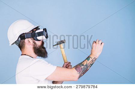 Builder And Renovation Concept. Man With Beard In Vr Glasses Holds Hammer, Light Blue Background. Hi
