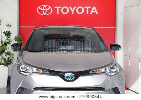 Toyota Car In The Store. The Emblem Toyota Logo On A Facade. Toyota Motor Corporation Is A Japanese