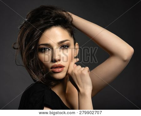Beautiful woman with brown hair. Attractive model with brown eyes. Fashion model with a smokey makeup. Closeup portrait of a pretty woman looks at camera. Creative hairstyle.