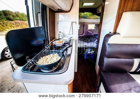 Cooking dinner or lunch in campervan, motorhome or RV. Preparing chicken  in a pan in camper van whe