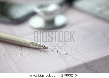 Medical Stethoscope Head And Silver Pen Lying On Cardiogram Chart Closeup. Cardio Therapeutist Pulse