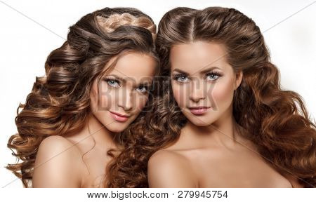 Beautiful models twins girls with shiny brown straight long hair. Women with Perfect Health Skin face smiling. Care and updo hair products. Youth, Spa and Skin Care Concept