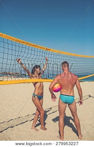 Woman And Man Doing Sport On Beach. Victory And Reward Concept. Young Sporty Active Couple Stand Nea