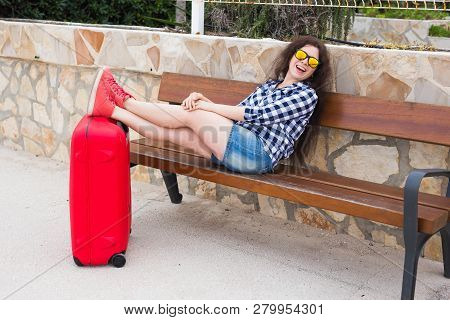 Holiday, Travelling And Rest Concept - Young Woman Resting With Feet On Suitcase