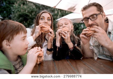 hungry family eating hamburgers, sitting at a table in a fast food restaurant