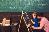 Pupil with teacher at school. Side view bearded father and son learn arithmetic. Daddy explaining equation to cute kid. poster