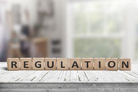 Regulation Sign On A Wooden Table In A Bright Offive In Daylight