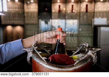 Hand holds Wine bottle in ice bucket. Wine bottle in bucket with ice. Champagne bottle in ice bucket