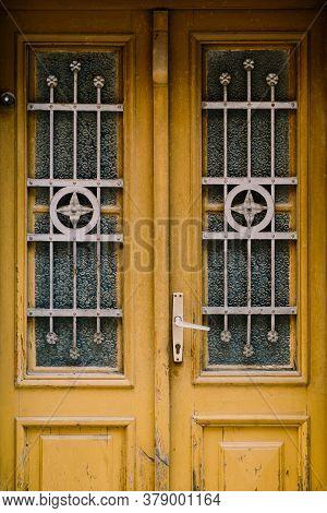 Old Wooden Doors With Original Metal Bars On The Windows.