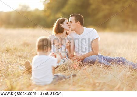 Family With Children Walking Outdoors In Summer Field At Sunset. Father, Mother And Two Children Son