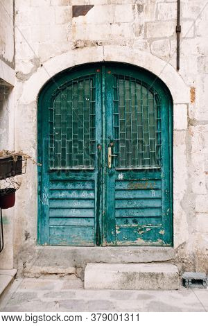 Old Closed Doors In Green With Bars On The Windows In The Oval Doorway.