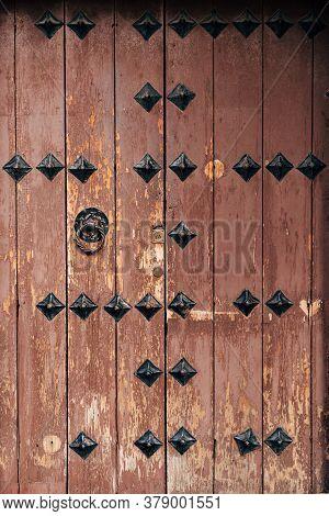 Brown Wooden Antique Door With Metal Rivets And Door Knocker.