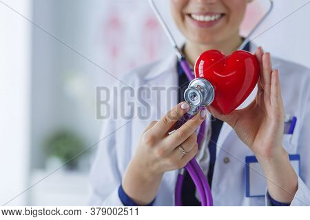 A Doctor With Stethoscope Examining Red Heart, Isolated On White Background