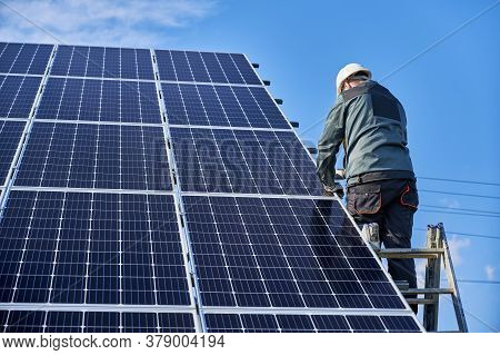 Back View Of Man Technician Standing On Ladder And Installing Photovoltaic Solar Panel. Male Worker