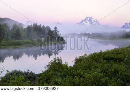 Foggy Covers The Snake River At Sunrise As Mt Moran Extends Above The Fog Bank In Grand Teton Nation
