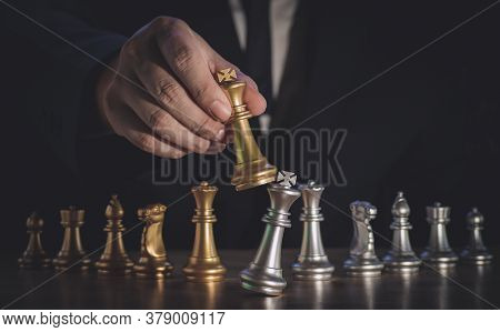 Hand Of Businessman Moving The Golden King Chess To Fighting Silver King Chess To Play Successfully