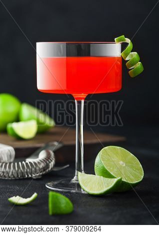 Cosmopolitan Cocktail In Modern Crystal Glass With Lime Peel And Fresh Limes With Strainer On Black