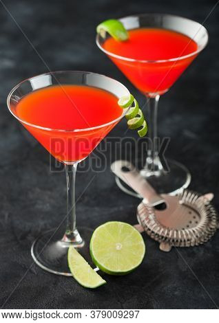 Cosmopolitan Cocktail In Classic Crystal Glasses With Lime Peel And Fresh Limes With Strainer On Bla