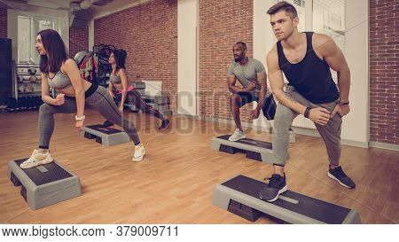Multiracial Sporty Athletes Working Together In Modern Fitness Club
