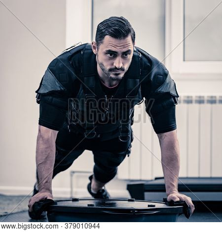 Strong Male Athlete In Ems Costume Doing Plank Exercise On Bosu Ball
