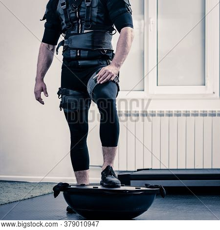 Legs Of Sporty Man In Electrical Muscular Stimulation Suit Standing On Ball