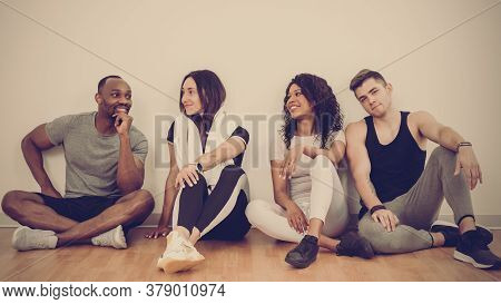 Portrait Of Four Happy Multinational Friends Siting On Floor In Gym After Training