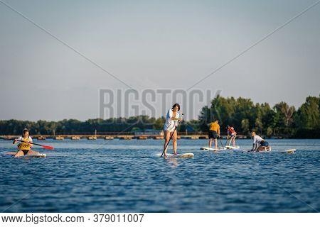 Dnepr, Ukraine- July 17, 2019: Active People Doing Yoga On Sup Boards