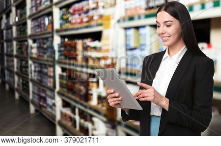 Wholesale And Logistics Concept. Manager Using Tablet Computer In Warehouse