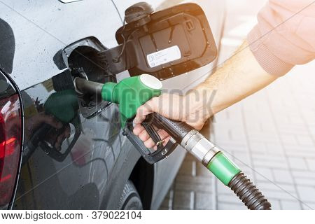 Refueling The Car At A Gas Station Fuel Pump. Man Driver Hand Refilling And Pumping Gasoline Oil The