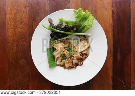 Stir Fried Noodles With Pork And Fried Egg In Top View