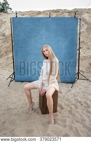Beauty Portrait Outdoors On Sand In Front Of Blue Background, Pretty Female Posing. Attractive Cauca