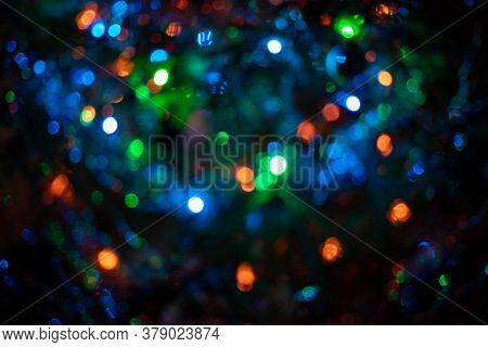 Defocused Blurred Christmas Tree Garlands Blue-green Color On Dark Background. Beautiful Multicolore
