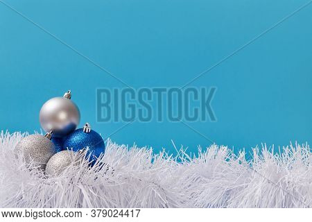 Christmas Decoration Composition. Blue And Silver Balls. Fluffy Tinsel. Copy Space. Blue Background.