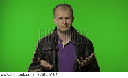 Confused Rocker Man In Brown Leather Jacket Looking At Camera With Embarrassed Expression, Have No I